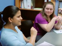 Two people sit on the same side of a desk and hold a collaborative conversation. One person is smiling with a hand raised and gesturing as they speak while the other listens.
