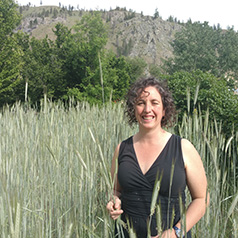 Sarah stands in a field of waist-high grass.
