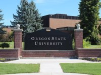 """A large black sign surrounded by red brick that reads """"Oregon State University"""" in white lettering."""