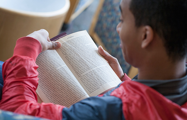 A person in a red and black sweatshirt reads a book with slightly worn and wrinkled pages.