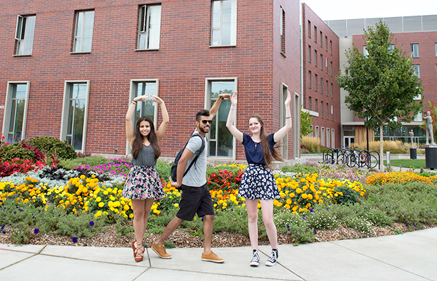 Three students use their bodies to form the letters OSU. Behind them, the campus blooms with bright flowers near the International Living-Learning Center.