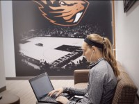 Sydney Weise does homework on a black laptop and uses earbuds. To her right is a large Oregon State basketball poster.