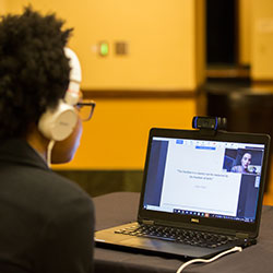 A person with curly hair and white headphones looks attentively at a laptop screen and listens to Ecampus WGSS student Victoria Keenan as she presents her research remotely at the Celebrating Undergraduate Excellence event.