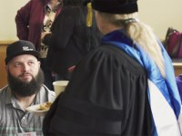 Matthew Baird speaks with an instructor at the Ecampus graduation reception.