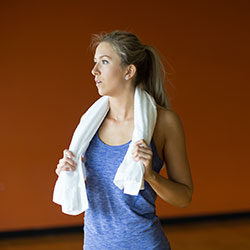 Calais stands in an exercise studio with an orange wall and looks into the distance to the left. She has her hair tied back and wears workout clothes and holds a white towel around the back of her neck.