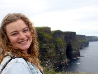 Carlee Sedgwick, a sustainability and sociology double major with Oregon State University Ecampus, stands with ocean cliffs behind her. She is in the environmental and natural resource option in the sociology bachelor's degree program.