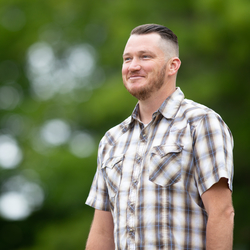 Horticulture grad Chris Holt smiles as he walks through the Oregon State campus with trees out of focus in the background.