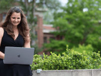 Maria Carpenter sits outside with a silver laptop on her lap. She is looking at the laptop and smiling. Green foliage and red brick buildings are visible in the background.