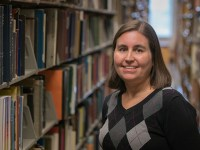 Mary Ellen Dello Stritto, assistant director of the OSU Ecampus Research Unit, is smiling near a bookshelf in the Valley Library.