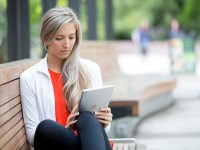 A woman sits on a bench outside and works on a smart tablet, completing an online application.