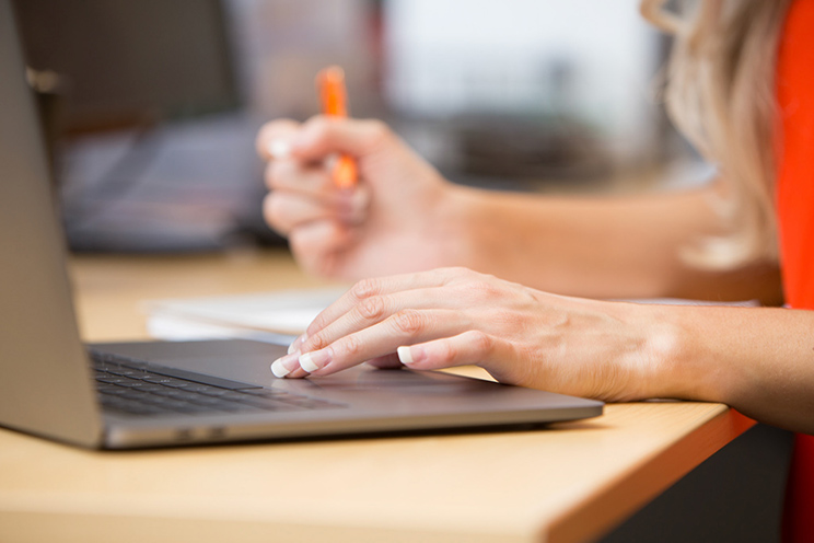 A woman uses a laptop while also writing on a notepad