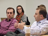 Students in the MBA in Organizational Leadership hybrid program meet face-to-face to discuss course content. One person is speaking while three people nearby listen.