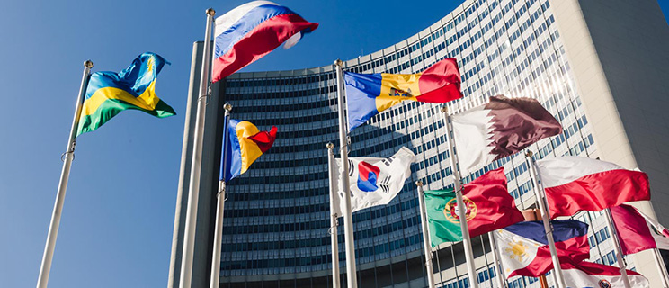 Eleven flags from various countries wave in front of a large, curved skyscraper building.