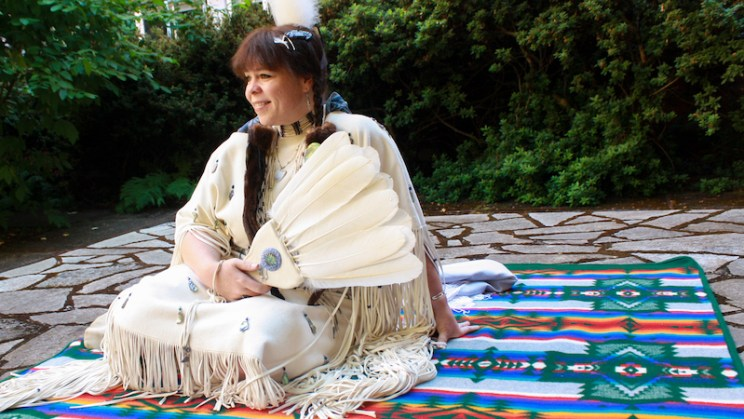 Samantha Chisholm Hatfield sits on a traditional tribal blanket in a traditional garment, holding a fan made of feathers.