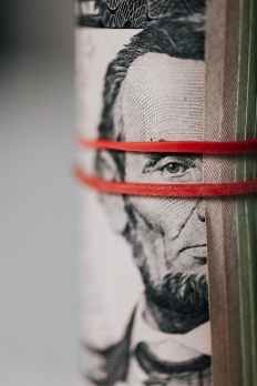 Picture of a roll of money being held together by red rubber bands. This denotes how money is wasted when people leave the company.