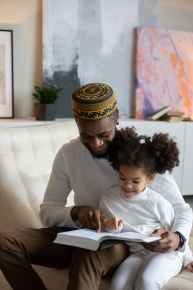 A single father reads to his daughter to help her learn a love for reading, which will pay off later by her being able to occupy herself while he works at home.