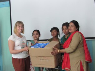 International volunteer Ms. Kati Hirvonen helps to hand over pads to school teachers. 5 schools were provided with sanitary pads