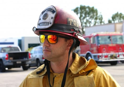 Adam Brown must wear his captain's jacket and helmet while in training. The color of a firefighter's helmet helps indicate their position. Adams' red helmet indicates to others on calls or at training that he is a fire captain. Adam also enjoys sporting a pair of sunglasses both at training and on his days off.