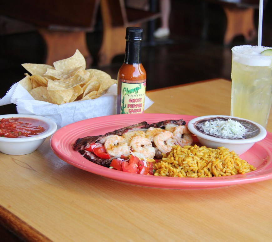 A table of a Mexican shrimp dish with rice and beans plus a salted margarita with chips and salsa.