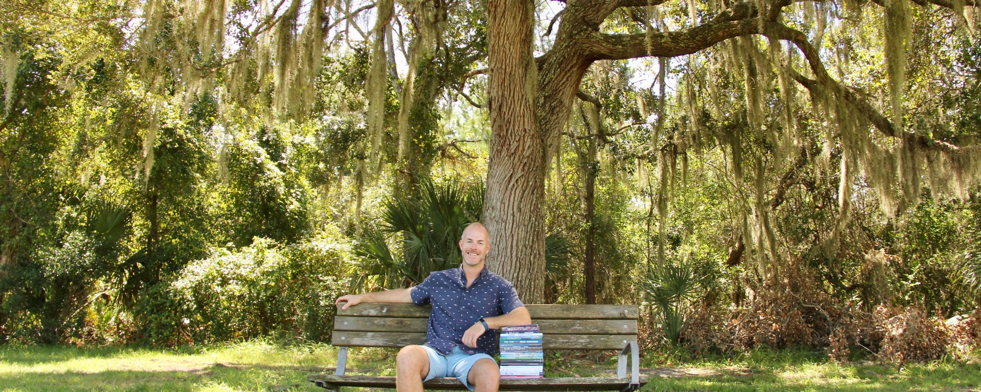 Author, Sean Donavan, sits under tree with stack of published books