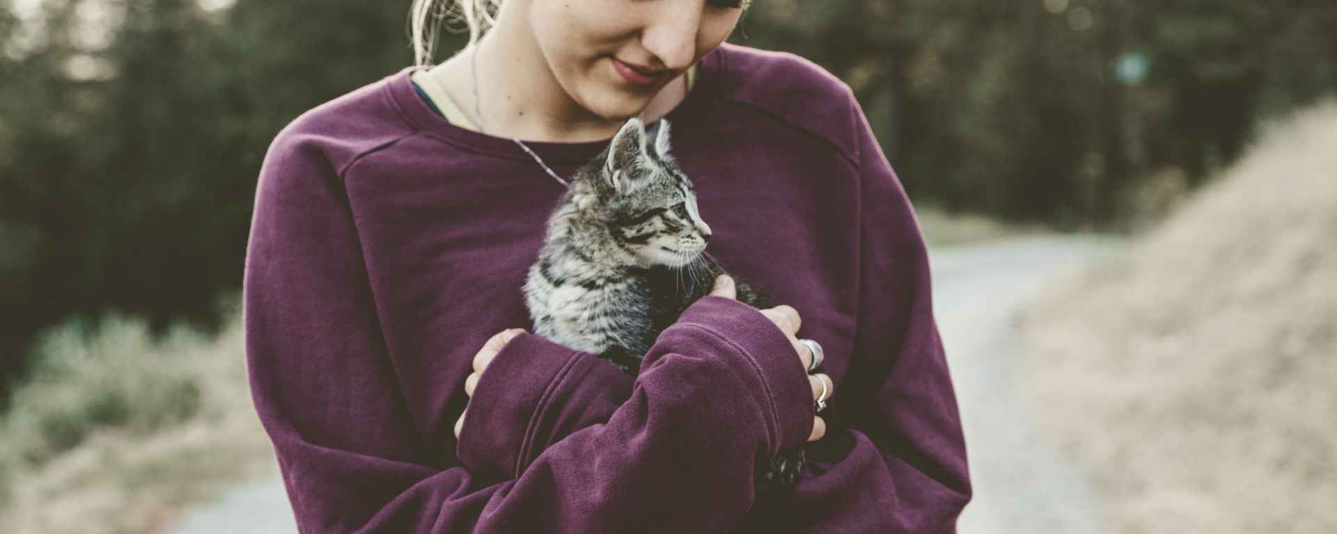 woman in purple sweater cuddling kitten outdoors in cold