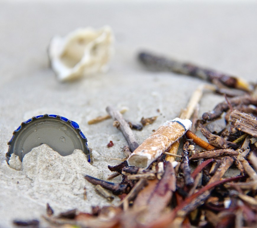 cigarette butt and garbage on sandy beach