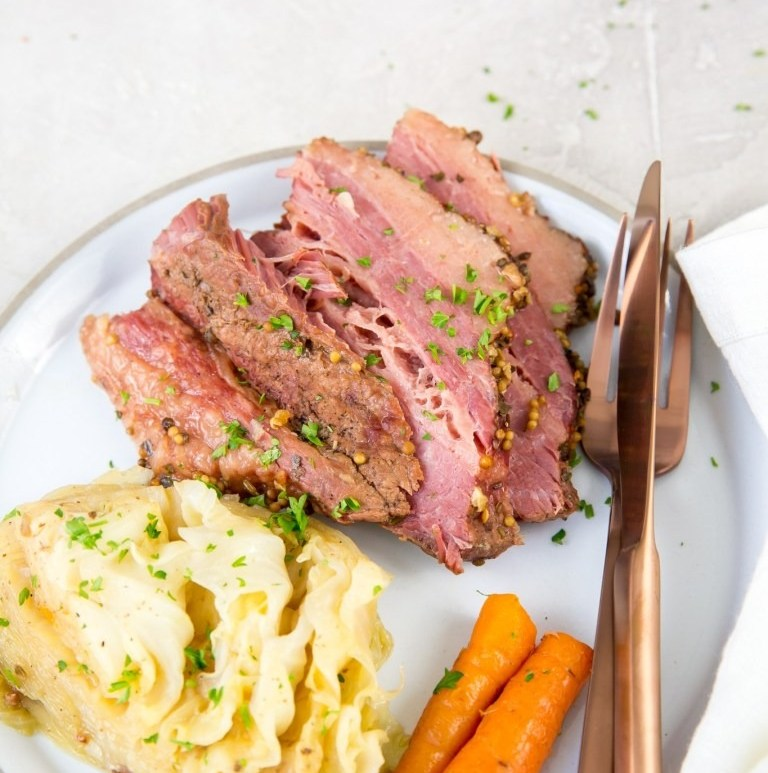 pressure cooker corned beef and cabbage with vegetables on white plate and table