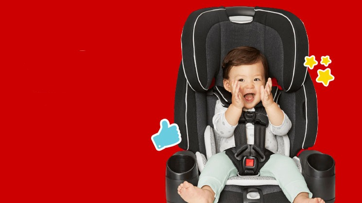 smiling baby in car seat on red background