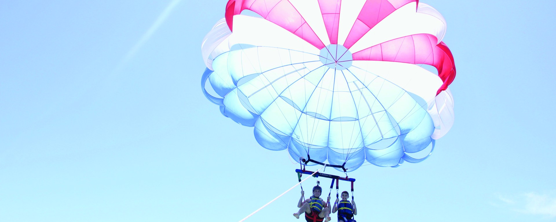 two boys parasailing with smiles on faces