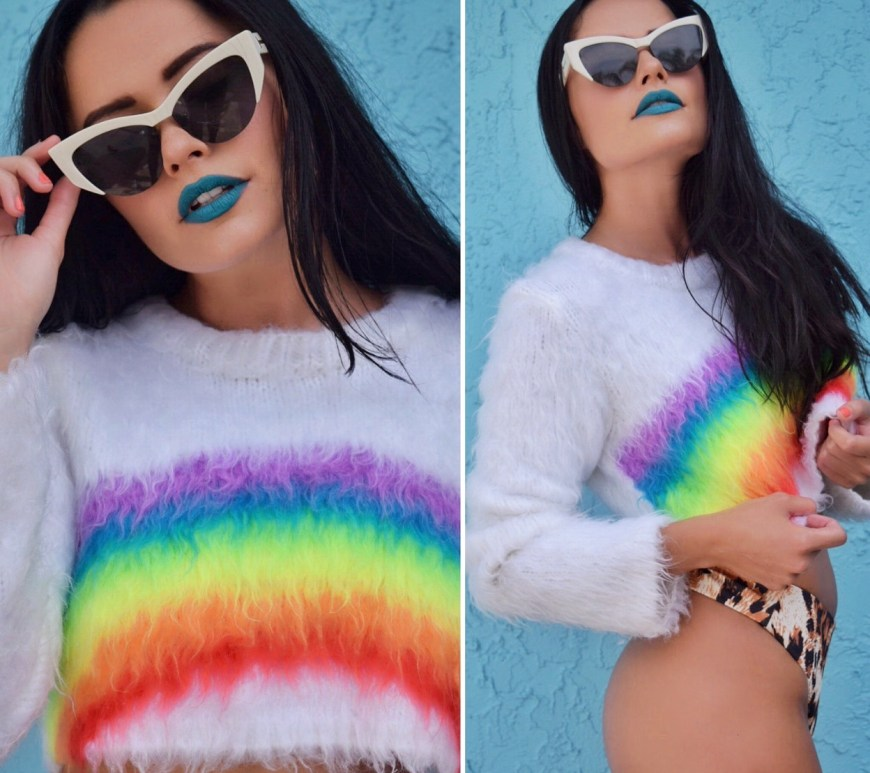woman with dark hair, sunglasses and blue lipstick in a rainbow sweater