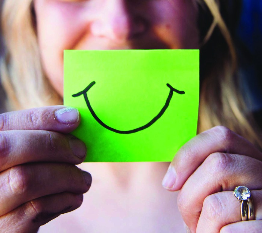 woman holding green post it note with smile drawn on in front of face
