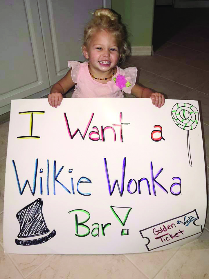 small girl holding Wilkie Wonka bar sign