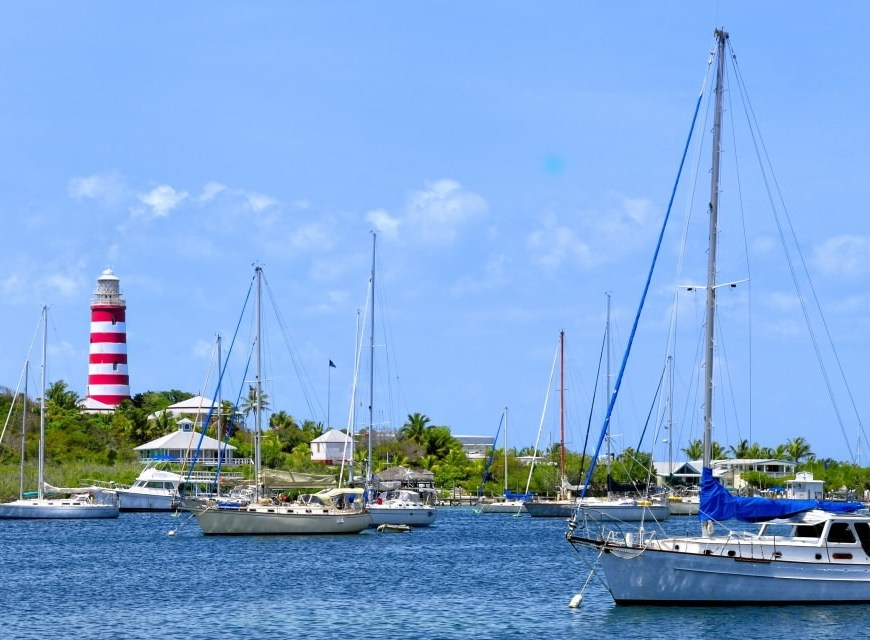 sailboats in water in front of small red and white lighthouse