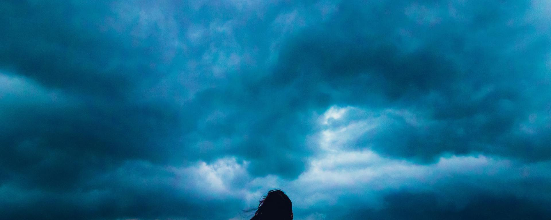 woman looking forward at dark blue storm clouds