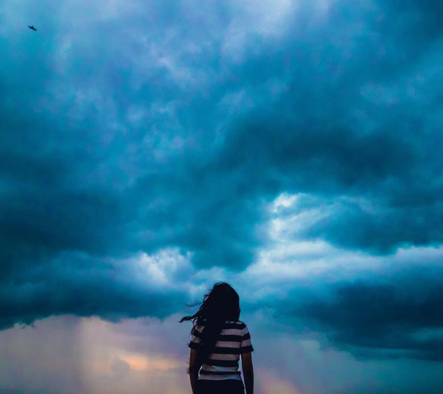 woman looking forward at dark blue storm clouds