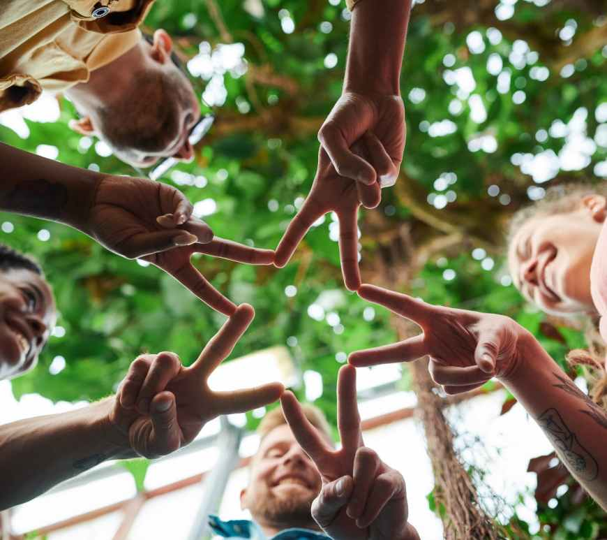 group of people forming star with their hands and fingers under green trees