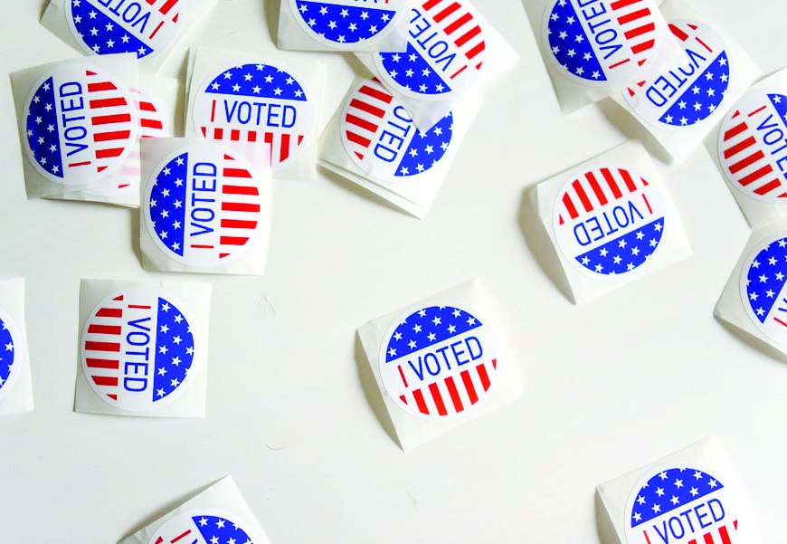 scatter of voting stickers on white table