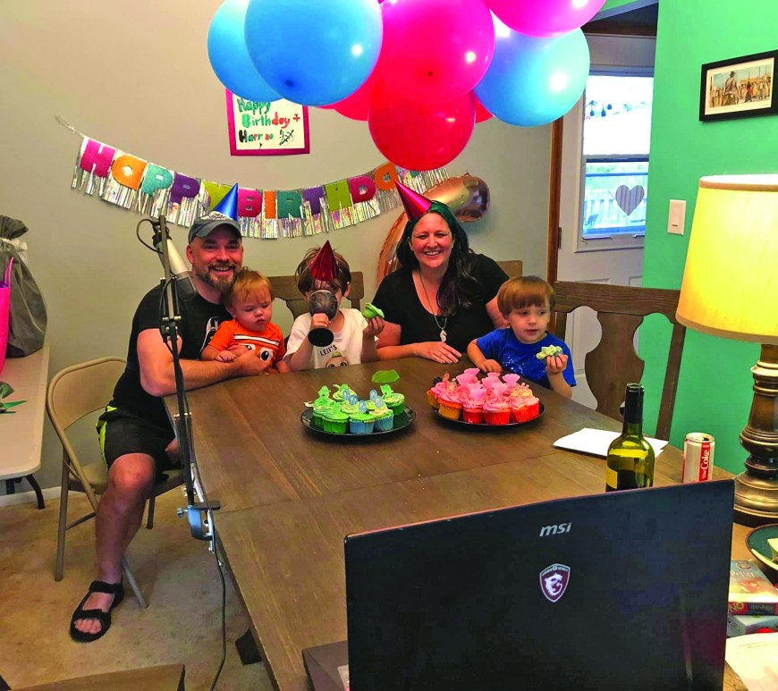 family having birthday party at kitchen table with virtual guests via zoom meeting