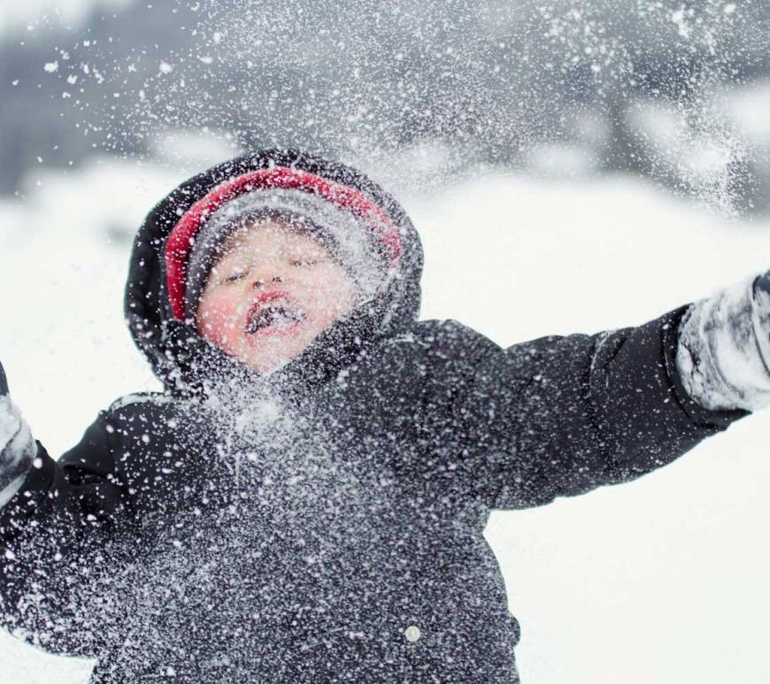 Happy young child covered in snow flakes