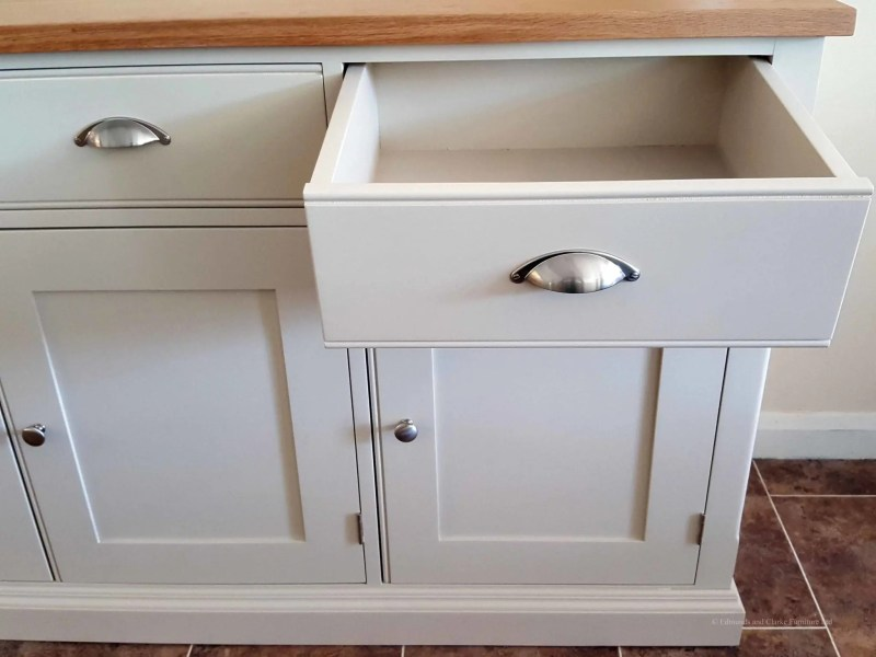 5ft Painted Sideboard handmade from Edmunds & Clarke Furniture. Painted in Dunwich stone with a solid square oak top, 3 drawers and 3 doors, image showing drw open with cup chrome cup handles and chrome knobs on doors. EDM029