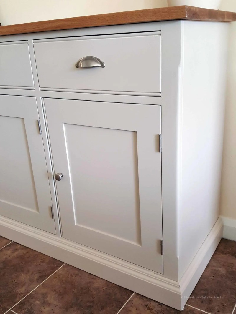 5ft Painted Sideboard handmade from Edmunds & Clarke Furniture. Painted in Dunwich stone with a solid square oak top, 3 drawers and 3 doors, image showing cup chrome cup handles and chrome knobs EDM029