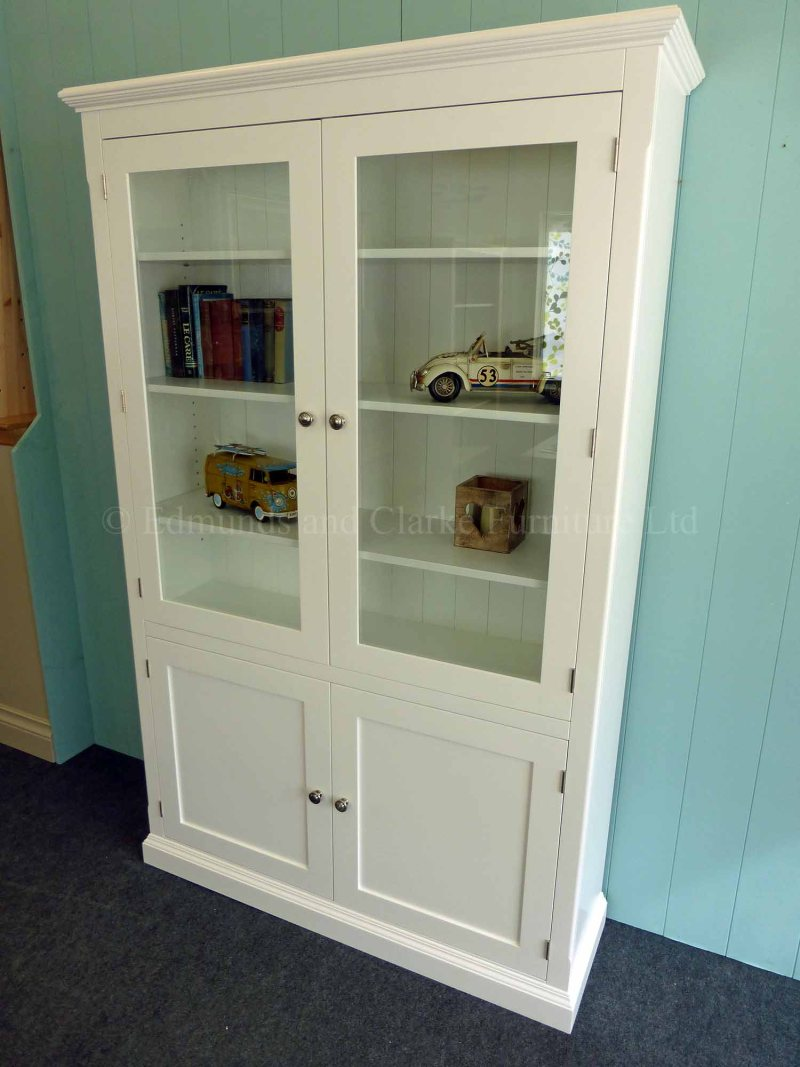 Edmunds Painted Glazed/Panelled Bookcase. Adjustable shelves with glazed top and cupboard below. Image is colour white and painted white. Different finishes available and different knob opt