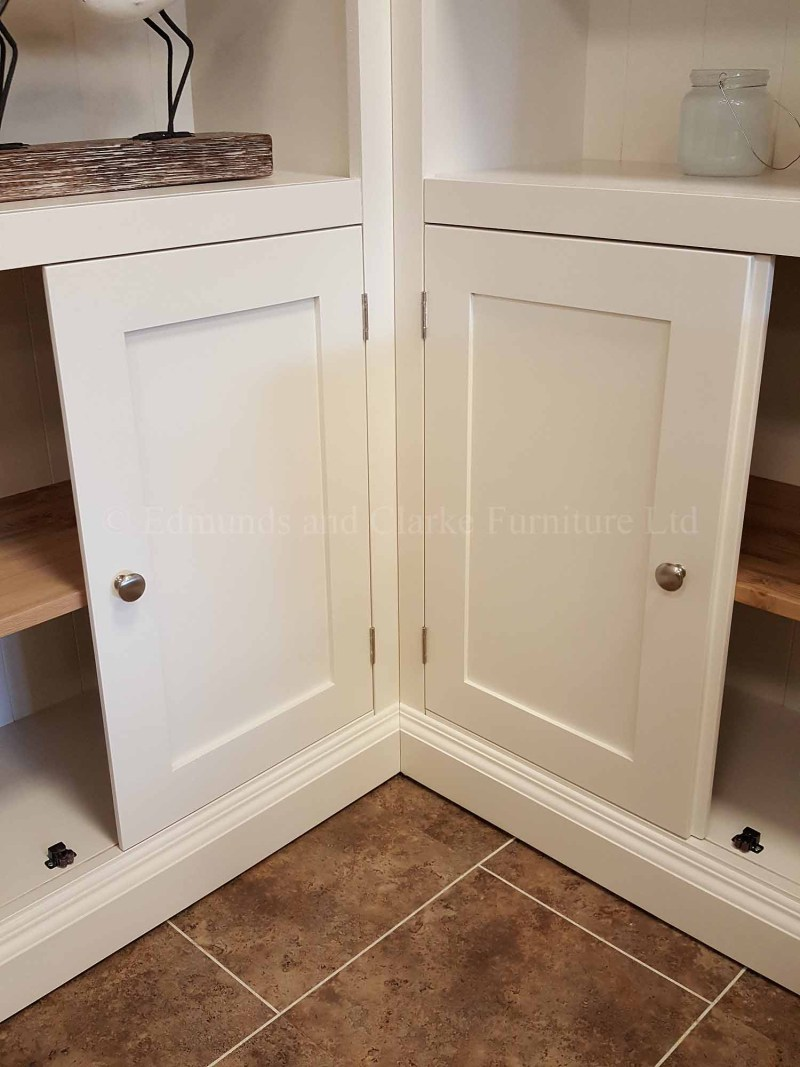 Painted white corner bookcase with cupboards below adjustable shelves above