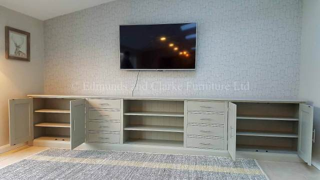 Long wide painted all over television entertainment unit with doors open, two adjustable shelves in each cupboard.