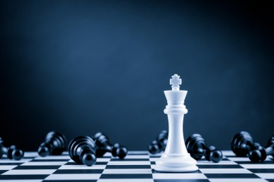 White Chess King among lying down black pawns on chessboard