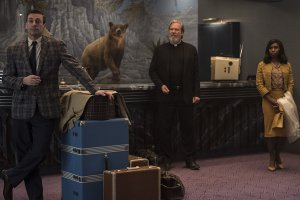 Three people checking into the El Royale Hotel