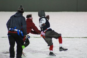 Students playing flag football in the snow