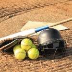 Softball balls, helmet, and bat at home plate