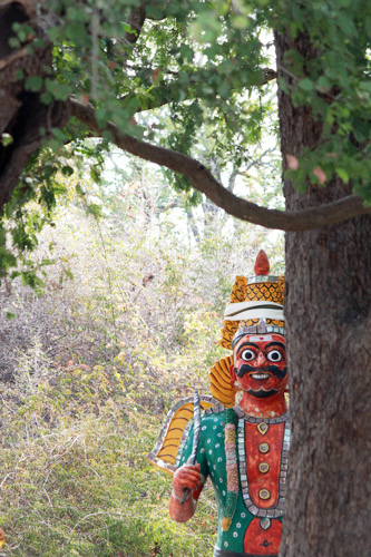 One of the terracotta guardian spirits beside a tree.