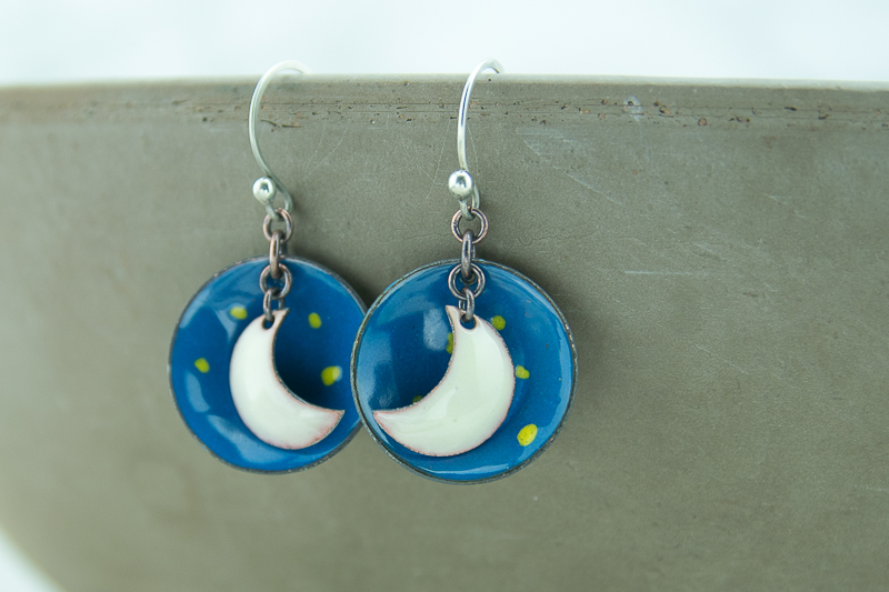 Blue starry sky and white crescent moon drop earrings created with torch fired enamel.